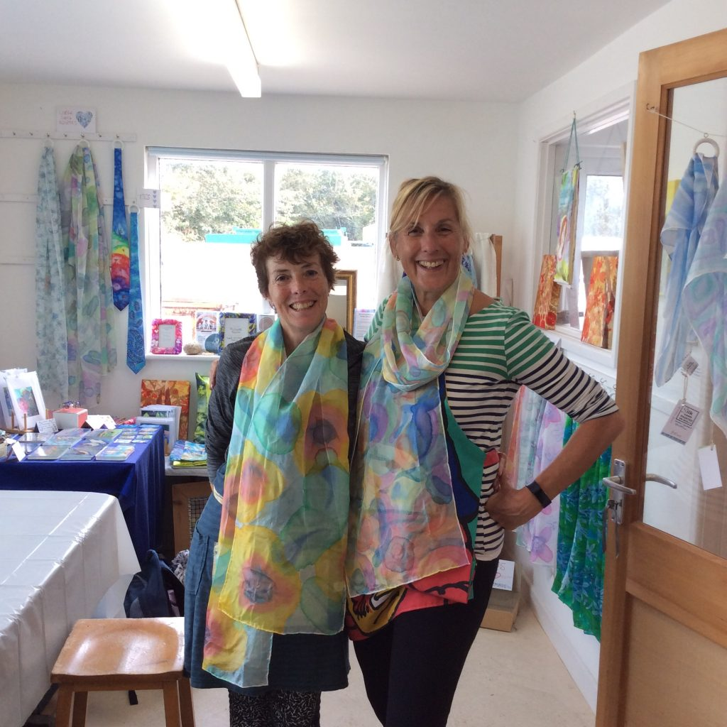 Two smiling women modelling their hand painted scarves
