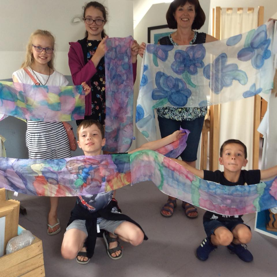 Family holding up their painted silk scarves